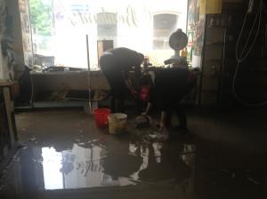"""Studenten und Einheimische helfen zusammen. Das Hochwasser wird mit Eimern aus """"Bernhard's Corner Shop"""" geschöpft."""