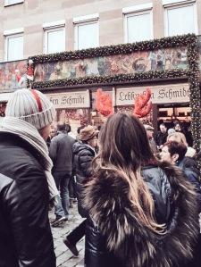 """Billiger als auf dem Christkindlmarkt gibt es echte Nürnberger Lebkuchen bei Lebkuchen Schmidt am Hauptmarkt - hier mit """"maskierten"""" Besuchern davor."""